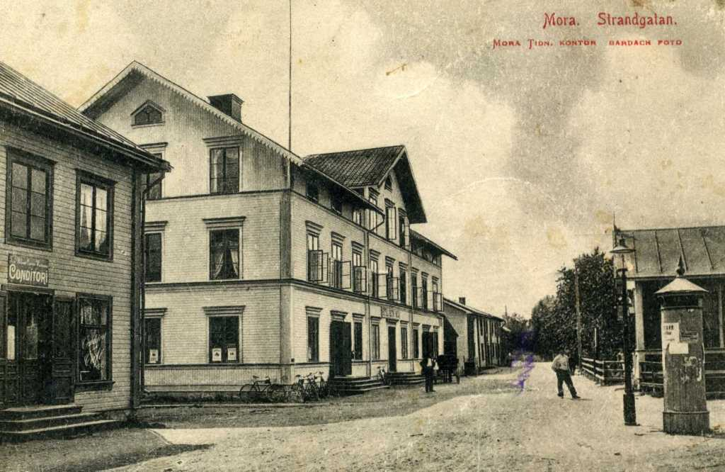 Fin bild med affischpelaren och B Hallgrens ateljé på Strandgatan. Conditori till vänster.